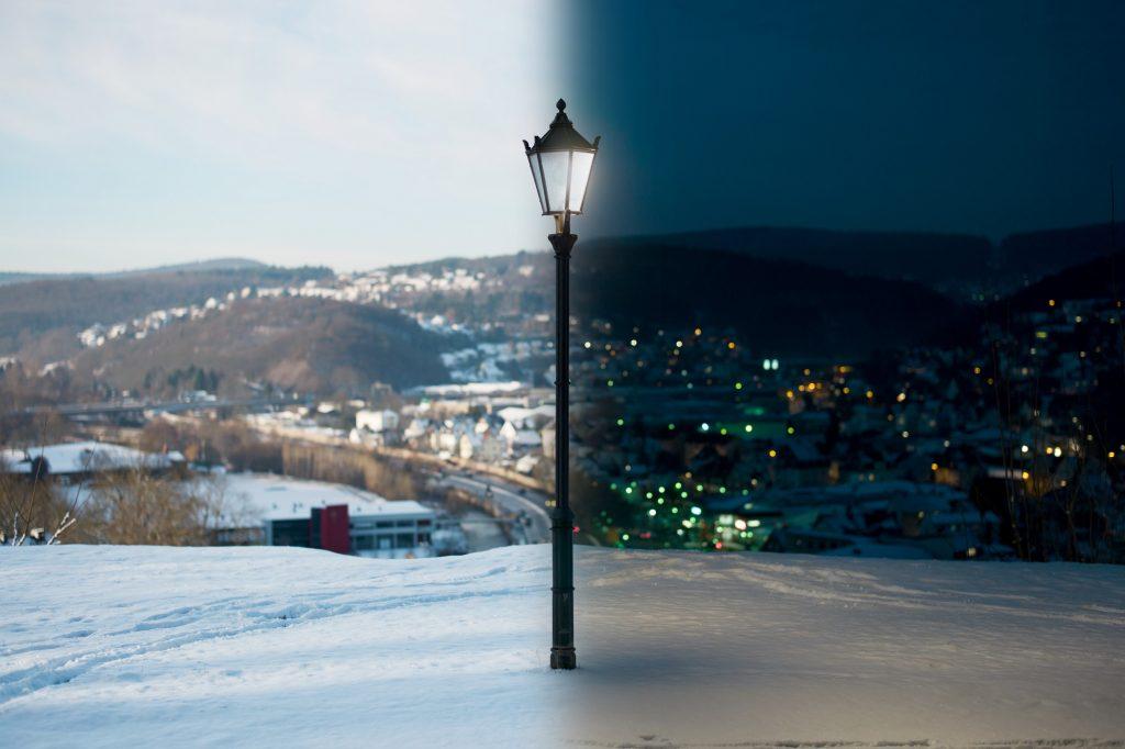 Eine leuchtende Straßenlaterne, die in der Mitte des Bildes steht. Das Bild selbst ist in Tag und Nacht unterteilt. Im Hintergrund ist ein Teil der Oranienstadt Dillenburg zu sehen. Auf der Tag-Seite ohne Beleuchtung, auf der Nacht-Seite mit Beleuchtung
