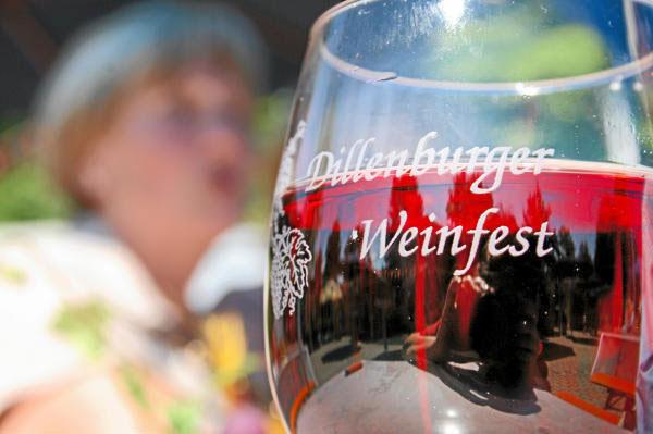 """Im Vordergrund ein graviertes Rotweinglas mit der Aufschrift """"Dillenburger Weinfest"""" im Hintergrund ist ein Mensch erkennbar."""