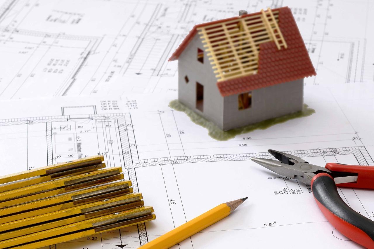 Bauskizze, Zange, Zollstock, Bleistift und ein Modellhaus