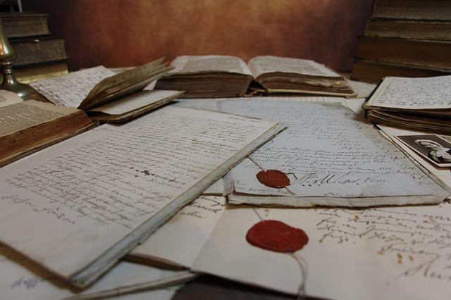 Das Bild zeigt eine Reihe von alten Urkunden und Büchern, die durcheinander liegen bzw. gestapelt sind.