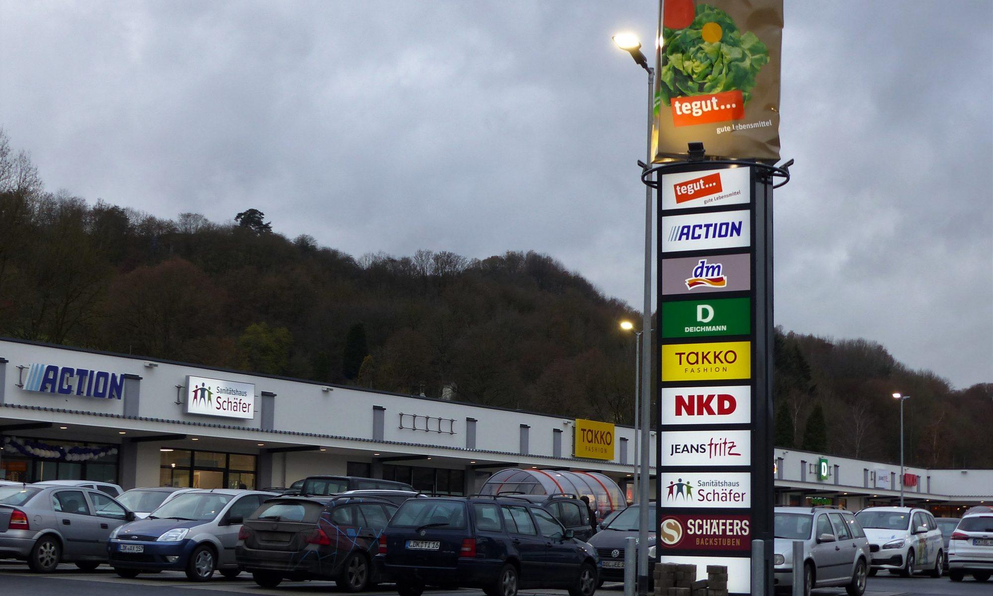 Ein Bild vom Parkplatz des Fachmarktzentrums mit einigen der Geschäften und der Werbestehle