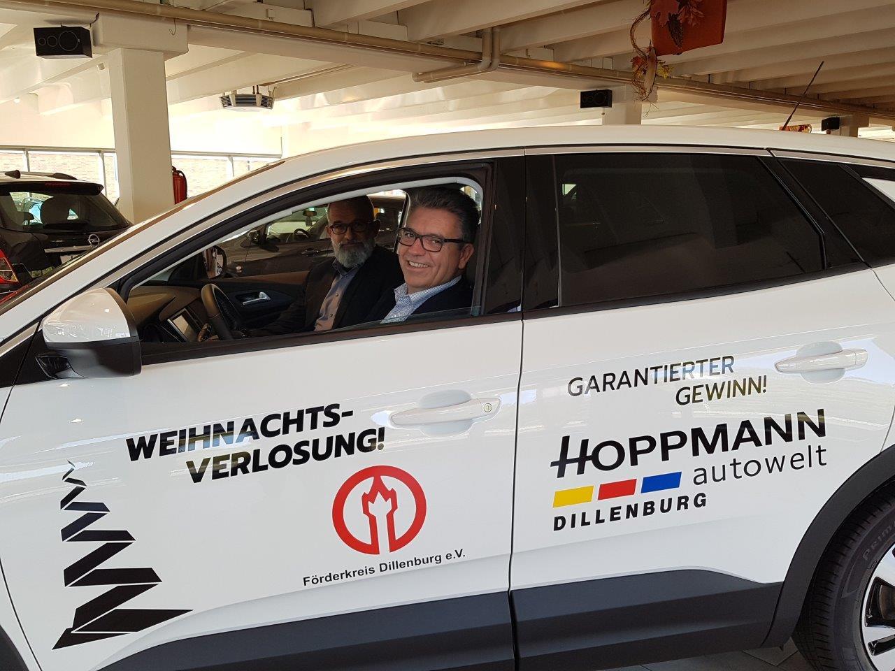 """Siegbert Theiss (Geschäftsstellenleiter Dillenburg Hoppmann Autowelt) stellt Bürgermeister Michael Lotz (2. Vorsitzender des Förderkreis Dillenburg) den Innenraum des Hauptgewinns vor und erläutert die umfangreiche Ausstattungslinie """"Innovation""""."""