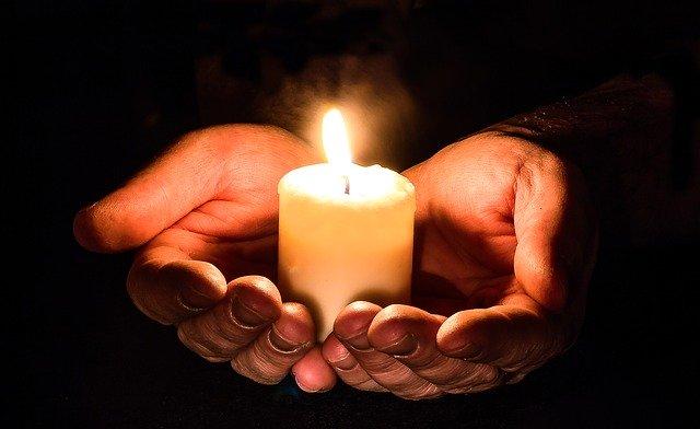 Eine Kerze, die in einer offenen Hand gehalten wird