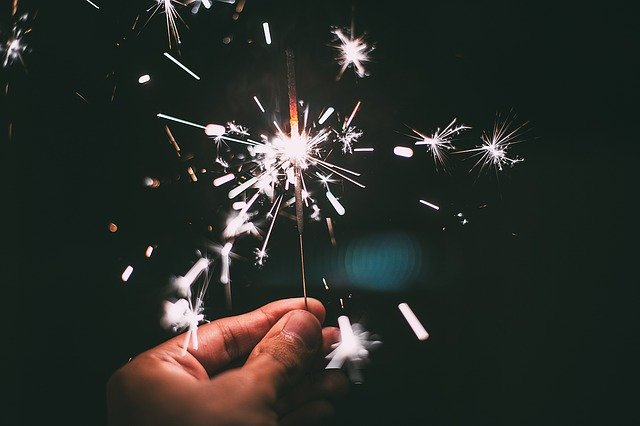 Eine Hand hält eine brennende Wunderkerze, Quelle: Pixabay