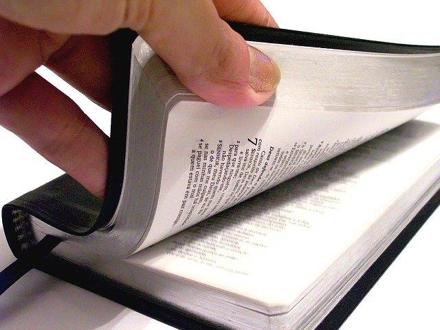 Eine Hand schlägt eine Bibel auf.Bild von Pedro Ivo Pereira Vieira Pedin auf Pixabay