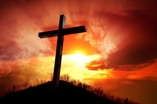 Bild Ein Kreuz auf einem Hügel vor einer untergehenden Sonnevon Germán R auf Pixabay