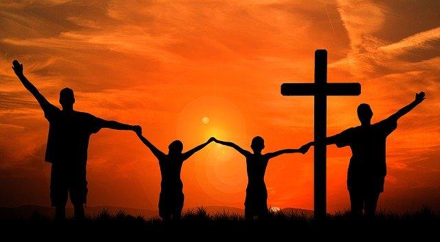 Ein Kreuz und Menschen, die sich an den Händen halten