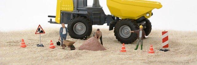 Spielzeugfiguren, -verkehrszeichen und Maschinen sind auf einer Sandfläche als Baustelle drapiert.