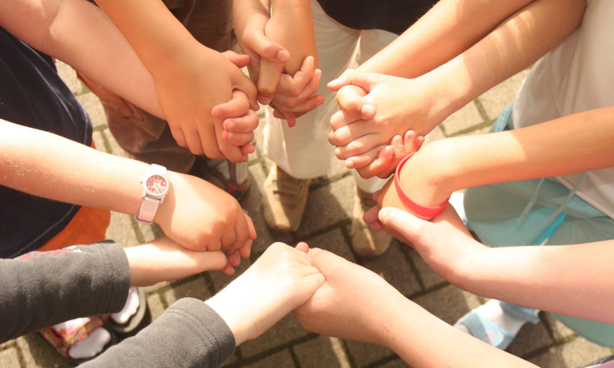 Gemeinsam... Kinder stehen im Kreis und man sieht, wie sie sich an den Händen halten.