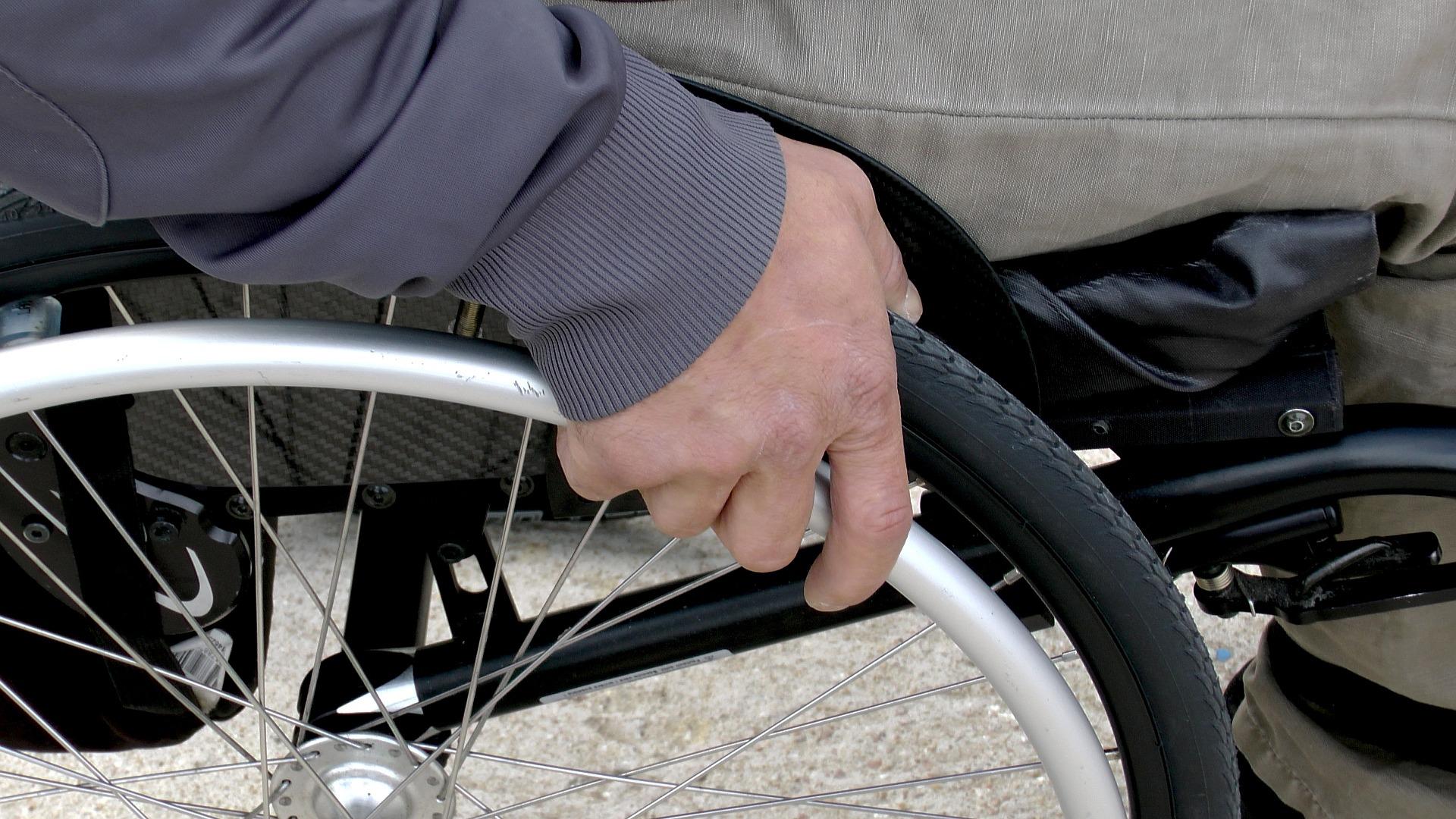 Ein Bildausschnitt mit einer Hand am Rad eines Rollstuhls